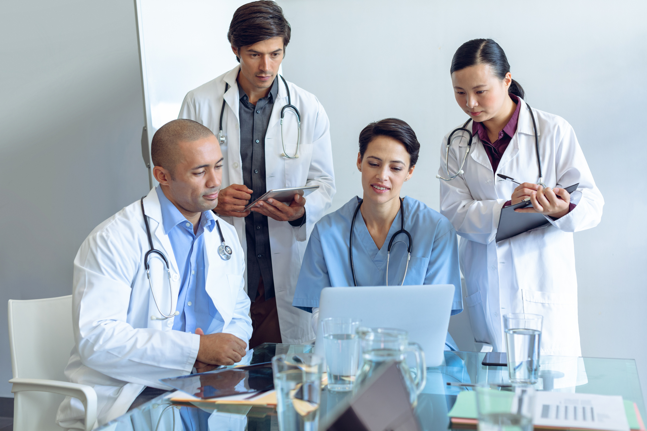 Front view of diverse medical team discussing over laptop at the table of conference room in hospital