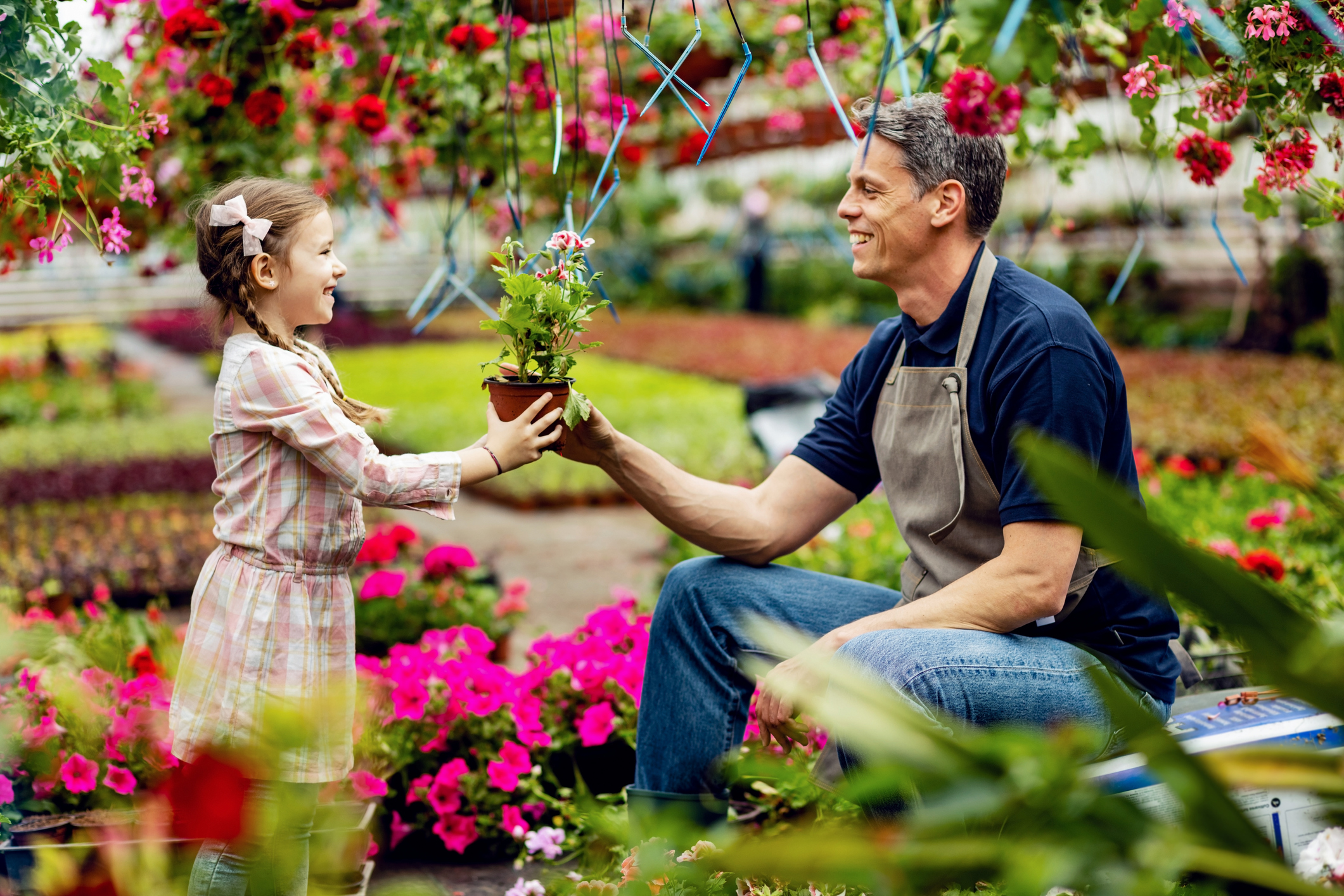 Happy father giving his small daughter potted flower while she's helping him in a garden center.
