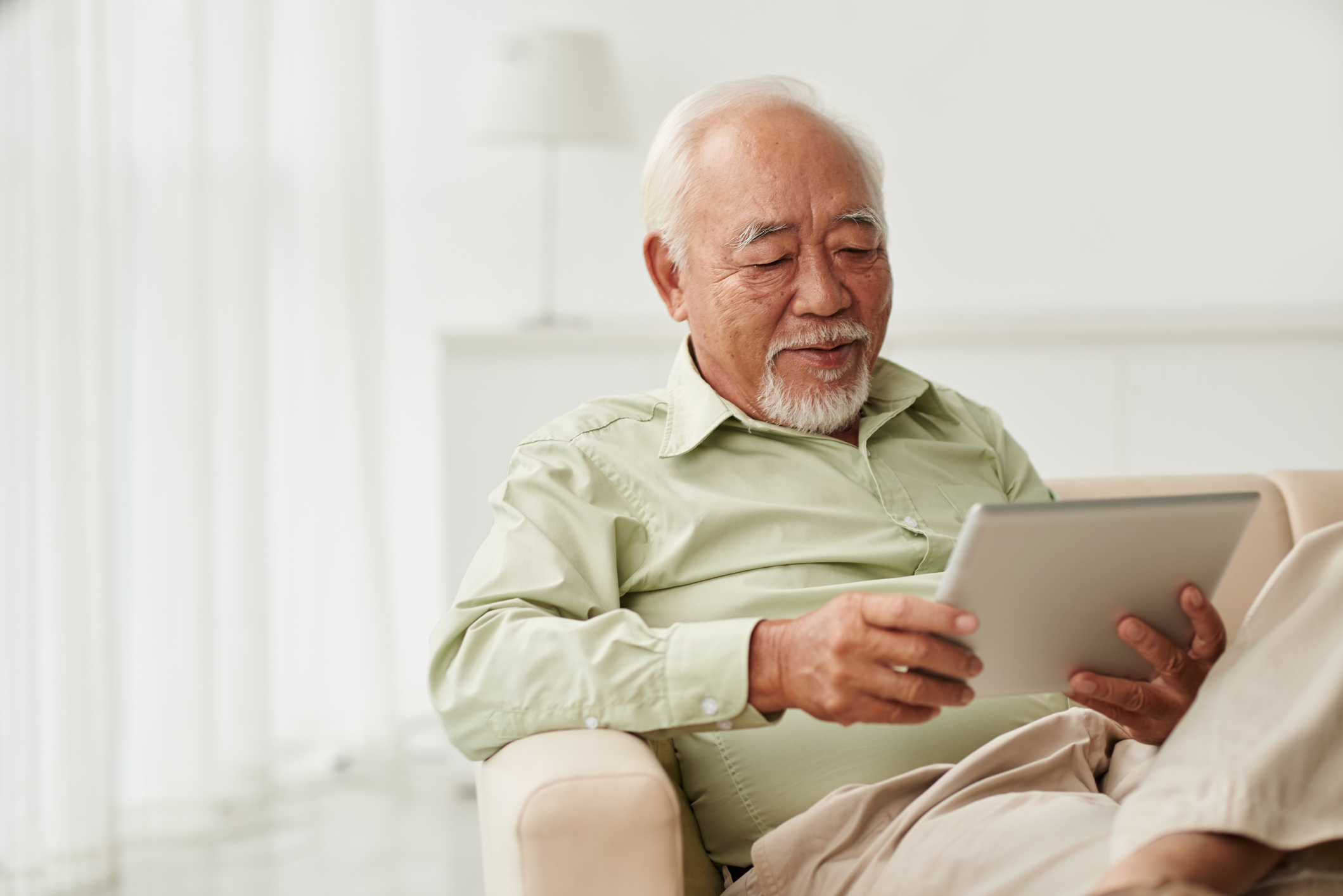 Senior Vietnamese man sitting on sofa and reading new on his tablet computer
